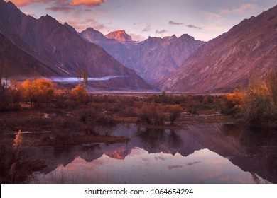 A beautiful sunset scene with mountains and reflection in water.