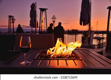 a beautiful sunset scene on a dock that has a firepit and two people enjoying a glass of wine