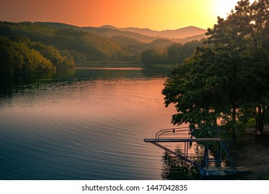 Beautiful sunset scene over the lake. In the distance, the peaks of the mountains are visible, and the diving board on the lake shore.
