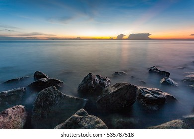 Beautiful sunset scenery with rocks at beach side. Blue sky and dusk, nature