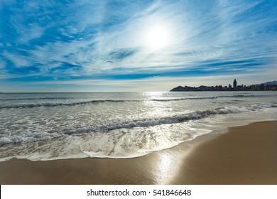 Beautiful sunset and sea waves at Benidorm Poniente beach in Alicante Mediterranean of Spain