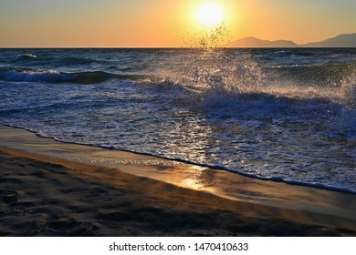 Beautiful sunset with sea and waves on the beach. Concept for summer holidays and sea vacation. Greece - island of Kos. Natural colorful background.