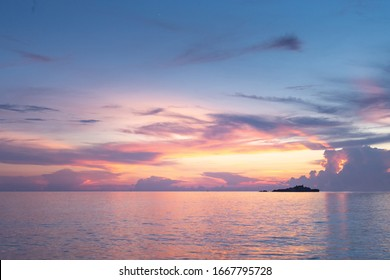 The beautiful sunset seascape at the beach which the sky has orange, purple, yellow and blue color and reflect to the sea. The atmosphere is calming to represent the romantic and warm scenic.
