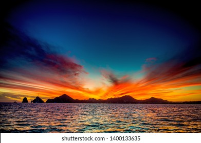 Beautiful Sunset of Seascape with Mountains silhouets. Sea off the Coast of Cabo San Lucas. Gulf of California (also known as the Sea of Cortez, Sea of Cortes. Mexico. Sunset over Cabo San Lucas.