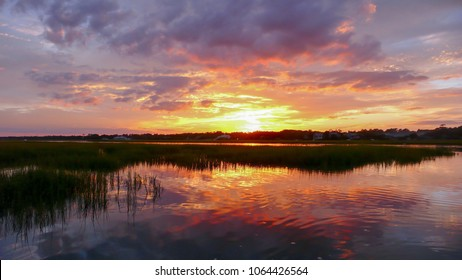 beautiful sunset setting over water and marshlands in the barrier island creekside waters of the South Carolina coast