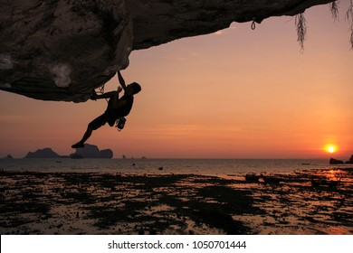 Beautiful sunset with shadow of unidentify Thai mountain climber climbing single pitch at the over hang cliff foreground at Tonsai, Railay beach  Krabi Province, Southern of Thailand