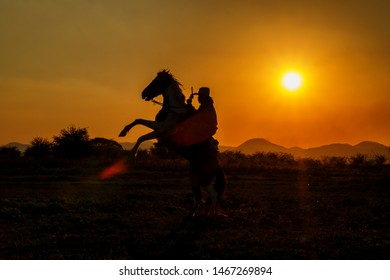 A beautiful sunset silhouette of cowboys riding horseback with mountain range background during golden hours on the field