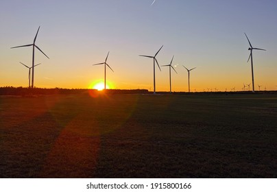 beautiful sunset with silhouette of wind wheels in the backlight