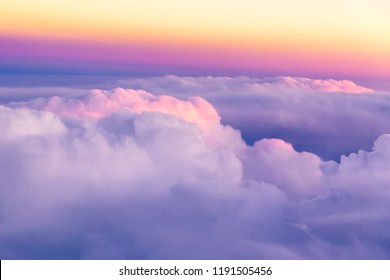Beautiful sunset sky above clouds with nice dramatic light. View from airplane window