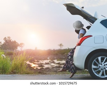 Beautiful sunset sky and clouds while young female traveler sitting on the white hatchback car. Travelling trip and Holiday relaxing concept.