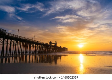 Beautiful sunset sky over the beach and ocean with wooden Oceanside pier - California, USA.