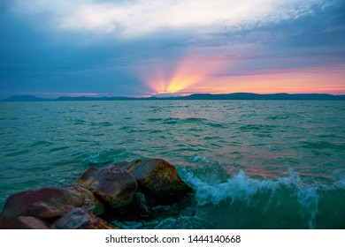 Beautiful sunset with sunbeam over the stormy lake Balaton in Hungary