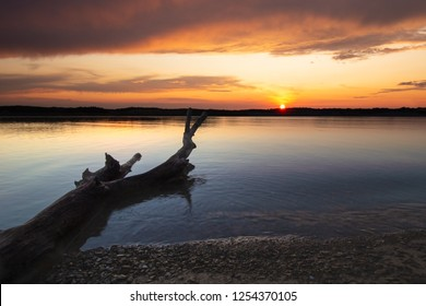 Beautiful sunset sunrise at Dale Hollow lake in Tennessee. Silhouette of a log extends into the water. Concepts of vacation, travel, relaxation, and peacefulness