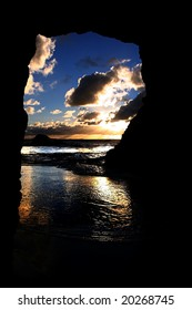 A beautiful sunset taken from within a cave at Maori Bay, Muriwai,on the West Coast of Auckland, New Zealand