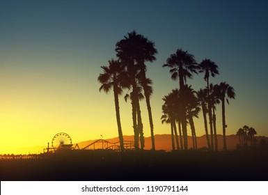 Beautiful sunset through the palm trees. Santa Monica beach, California, USA. Retro vintage colours