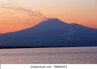 Beautiful sunset twilight on Agnone Bagni sea beach with smoky Etna volcano in far (Siracusa, Sicily, Italy)