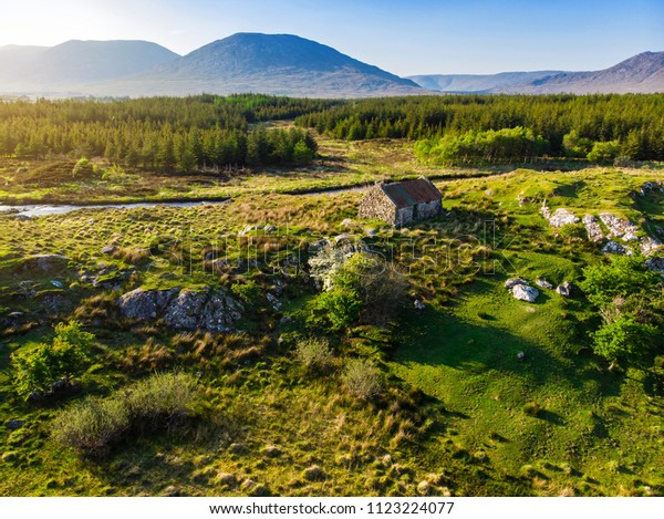 Beautiful sunset view of Connemara region in Ireland. Scenic Irish countryside landscape with magnificent mountains on the horizon, County Galway, Ireland.