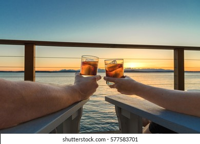Beautiful sunset view from the deck, couple holding up glasses to toast.