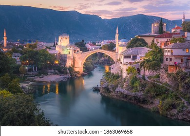 A beautiful sunset view of the iconic Stari Most bridge, Neretva River and old town of Mostar, Bosnia and Herzegovina with mountain backdrop. - Shutterstock ID 1863069658