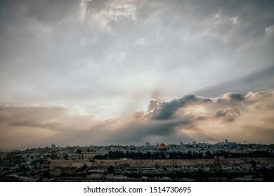 Beautiful sunset view of Jerusalem Old City from the Mount of Olives. Sky with sun rays, evening light