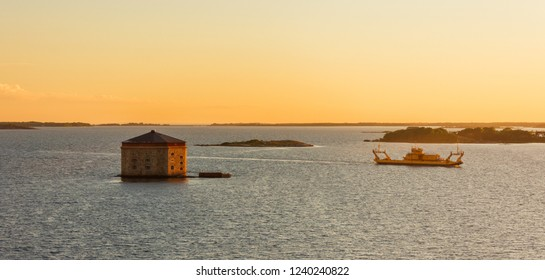 Beautiful sunset view on Godnatt naval keep (fortress in the sea for defense of naval harbor) and vessel in the Baltic Sea near Karlskrona, Sweden. Part of the UNESCO World Heritage Site Karlskrona.