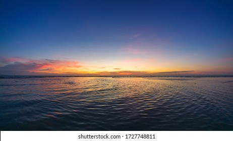 Beautiful sunset view on the ocean with waves and reflection.
