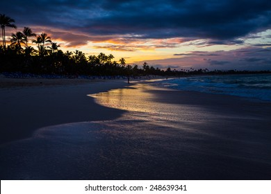 Beautiful sunset view of surf at beach with golden glow of sun reflecting off of water.