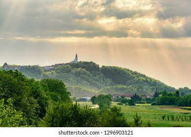 Beautiful sunset in Vipava valley, Slovenia. Belltower and small town on the hill with green sunny valley and vineyards.