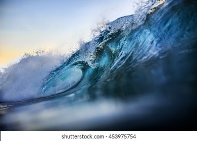 Beautiful sunset waterscape. Big surfing bright vibrant wave closing with nobody. An ocean tropical scenery at evening or morning time. Rip-curl in Indonesian Island Bali for watersport background.