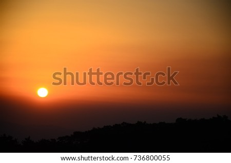 Beautiful sunset,orange sky,dark mountains silhouette.Evening nature view.Golden background with contrast sunlight.Hot yellow scenic dusk.Summer,autumn valley inspirational colorful landscape.