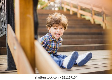 Beautiful sunshine toddler boy sitting on old wooden stairs and laughing joyfully while looking at camera. Portrait of adorable happy baby playing alone outside on warm summer day. Horizontal image.