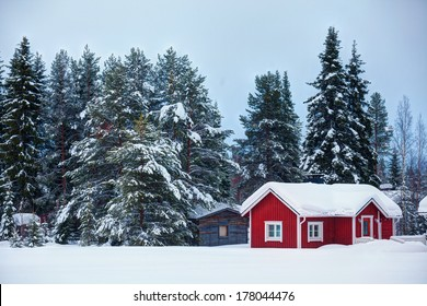 Beautiful super Finnish winter landscape with red wooden finnish house in winter covered with snow.