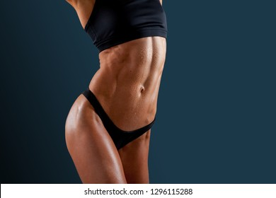 Beautiful super fit young woman showing off her perfect muscular ripped abs. Fitness model. Perfect Slim Body. Studio shot. Fitness trainer with ideal abdominal belly.