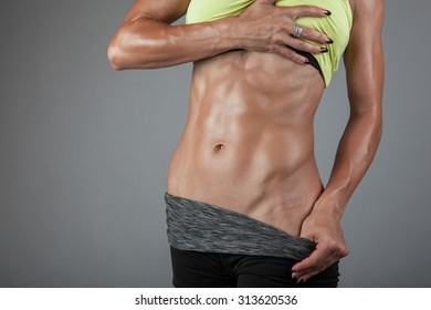 Beautiful super fit young woman showing off her perfect muscular ripped abs. Fitness model. Perfect Slim Body. Studio shot
