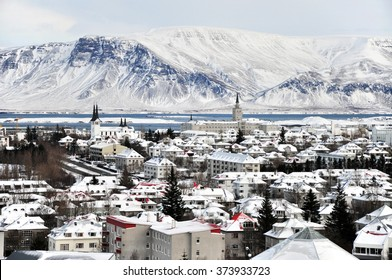Beautiful super wide-angle aerial view of Reykjavik, Iceland in winter with harbor and skyline mountains and scenery beyond the city, seen from the observation desk in Perlan.
