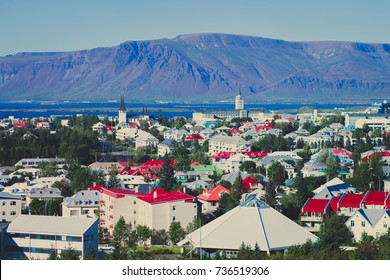 Beautiful super wide-angle aerial view of Reykjavik, Iceland with harbor and skyline mountains and scenery beyond the city, seen from the observation tower of Hallgrimskirja church, summer sunny day