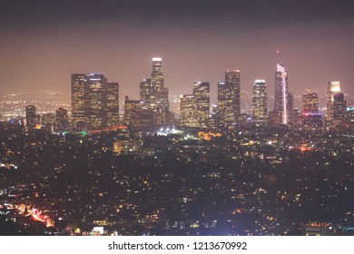 Beautiful super wide-angle night aerial view of Los Angeles, California, USA, with downtown district, mountains and scenery beyond the city, seen from the observation deck of Griffith Park observatory