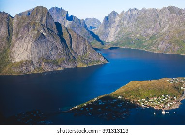 Beautiful super wide-angle summer aerial view of Reine, Norway, Lofoten Islands, with skyline, mountains, famous fishing village with red fishing cabins