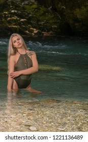 Beautiful supermodel woman posing in swimsuit in the colorful  river