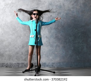 """Beautiful super-star girl in dress and """"MOTHER'S HEELS"""" with microphone on grey background"""