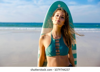 Beautiful surfer girl on the beach with her surfboard