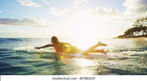 Schönes Surfer-Mädchen, das in den Sonnenuntergang paddelt