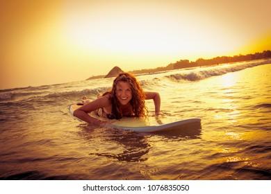 Beautiful surfer on sunset at  Weligama beach , Sri Lanka.  It coast of Indian ocean is the best surf paradise in Sri Lanka