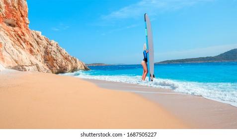 Beautiful surfer woman on the beach at sunny day - Clear water sea and orange sand beach - Kaputas Beach, Mediterranean Sea, Antalya