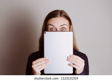 Beautiful surprised blonde woman holding tablet
