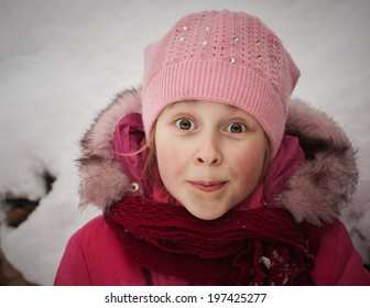 Beautiful surprised happy girl in the red jacket in the winter.