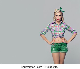 Beautiful surprised woman, dressed in pin-up style. Caucasian blond model posing in retro fashion and vintage concept studio shoot, on grey background. Copy space area for advertise, slogan or text.