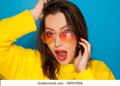 beautiful surprised woman with orange sunglasses on blue background