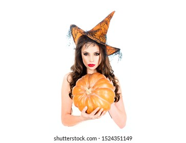 Beautiful surprised woman posing in witches Halloween costume - isolated on white background. Secrets of magic. Wizard. Beautiful young woman in witches hat with bright Halloween makeup