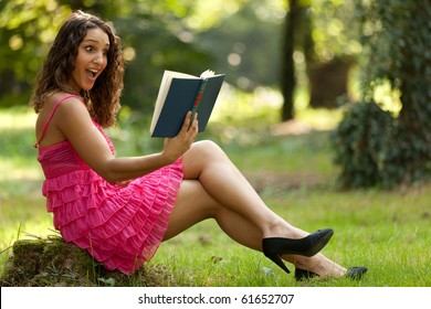 beautiful surprised woman reading book in nature